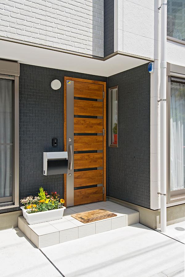 明るい木製ドアがシンプルな外観に映えます