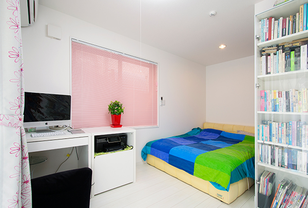 寝室です。ホワイト基調の室内に、ピンクのブラインドが優しい雰囲気