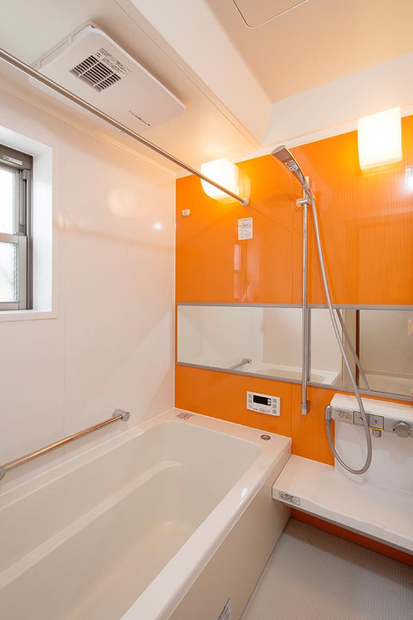 ビビッドなオレンジ色が差し色になっているバスルームです