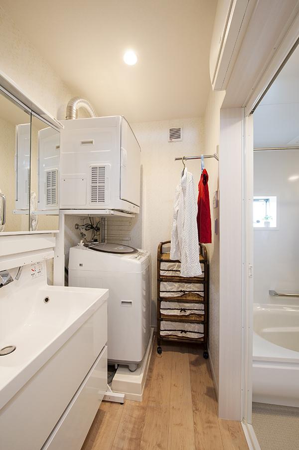 乾燥の早いガス乾燥機のある洗面室。服をかけるフックでスペースを活用